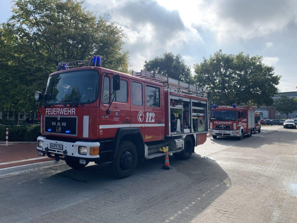 zwei Löschwagen der Feuerwehr stehen vor einer Bushaltestelle.
